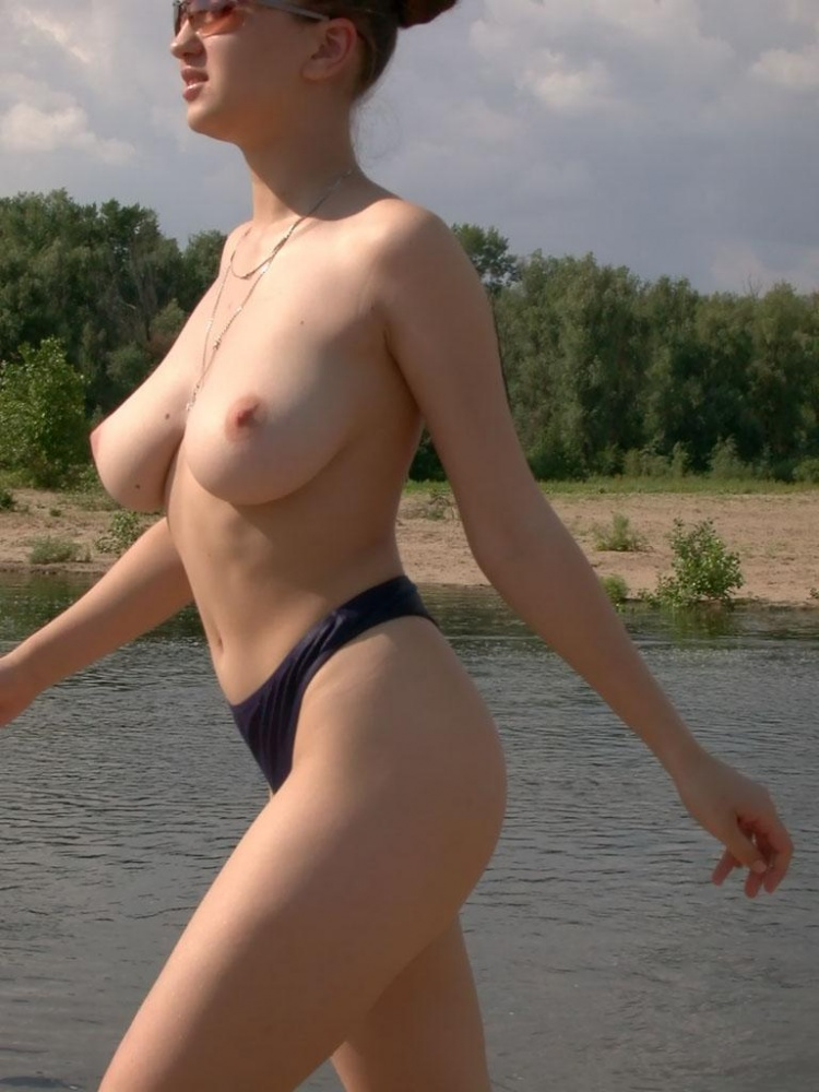 Busty girl on river beach