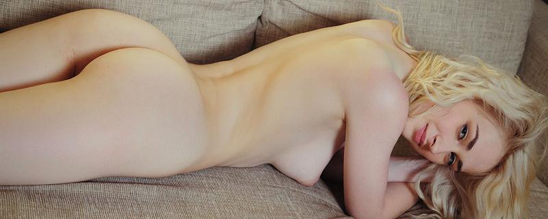 Innes lying naked on the sofa