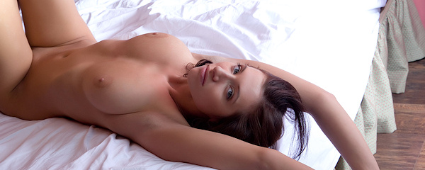 Simone lying naked on bed